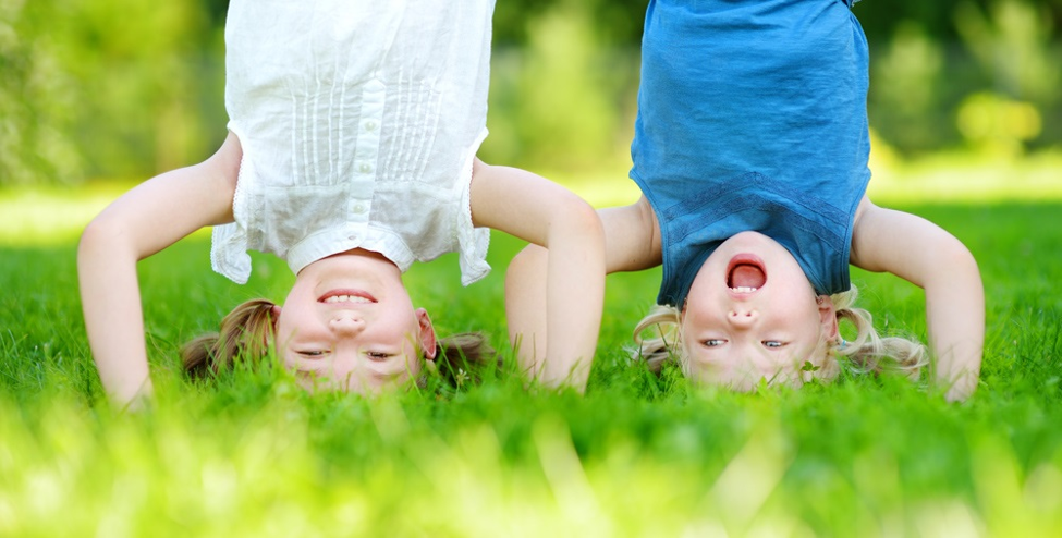 two little girls doing handstands in the grass